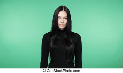 Young flirty brunette woman in a black shirt playing with the hair