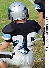 Young Football Player on Sidelines