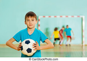 Young football player ready to throw soccer ball
