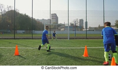 Young football players training to score goals - Two preteen...