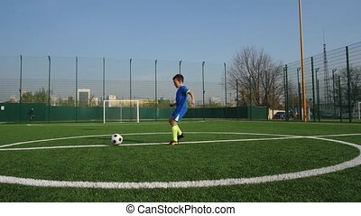 Young footballer taking pass and running to goal - Close-up ...