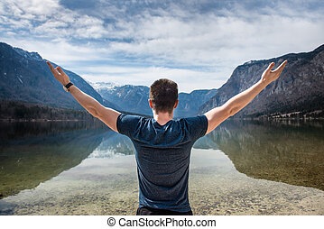 young freedom man hands up on a mountain lake