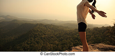 young freedom woman enjoy the view at mountain peak cliff