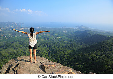 young freedom woman open arms on mountain peak