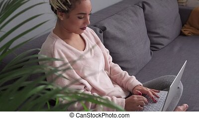 Young freelancer woman working on laptop computer on...