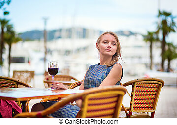 Young French woman drinking red wine