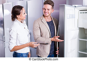 young friendly couple choosing new refrigerator in hypermarket