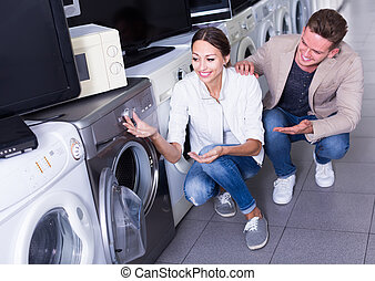 Young friendly couple choosing washing machine in hypermarket