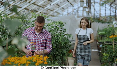 Young friendly woman gardener talking to customer and giving...
