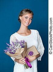 Young friendly woman smiling and holding gift and flowers. Young happy female model in white dress on blue background