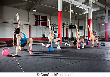 Young Friends Doing Stretching Exercise In Gym