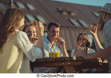 Young friends eating pizza outdoors