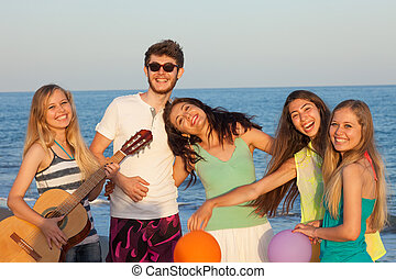 Young friends enjoying beach party with balloons and playing guitar, standing on the beach, blue sea and sky behind them.