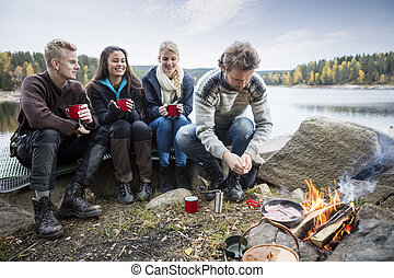 Young Friends Enjoying Camping On Lakeshore - Young friends...