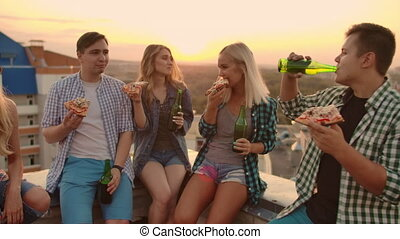 Young friends enjoying pizza during sunset on the roof