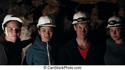 Young friends explorers looking at camera in a dark cave,...