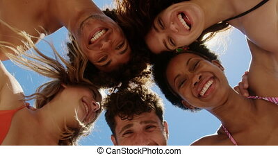 Low angle view of young multi ethnic friends forming huddle while Low angle view of young multi ethnics friends forming huddle while smiling and looking at camera at beach in the sunshine at beach in the sunshine 4k