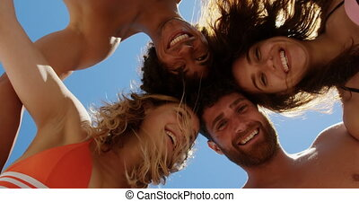 Low angle view of young multi ethnic friends forming huddle while smiling and looking at camera at beach in the sunshine 4k