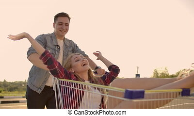 Young friends having fun on shopping trolleys. Multiethnic...