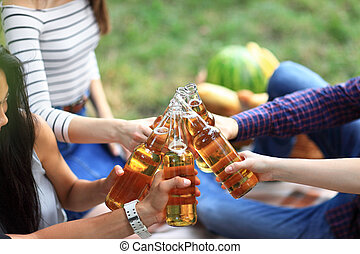 Young friends having fun outdoors, clinking bottles of beer...
