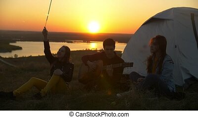 Young friends having fun with sparklers and songs with guitar at sunset outdoors