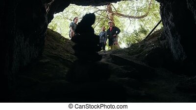 Young friends hikers standing at the entrance of the cave in...