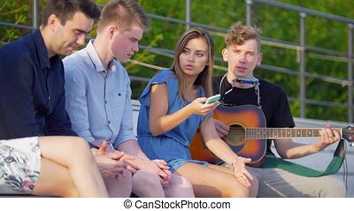 Young friends hipsters have a rest in the park and listen to songs with a guitar