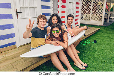 Young friends holding woman on top of surfboard