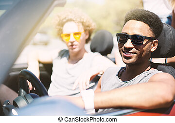 Young friends in cabriolet car ready to vacation