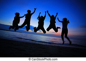 Young friends jumping on the beach