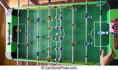 Young friends or students having fun together playing table football in slowmotion. Top view of game