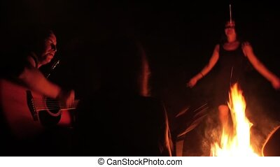 Young friends playing a guitar, girl dancing by the bonfire at night