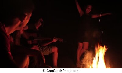 Young friends playing and dancing by the campfire at night,...