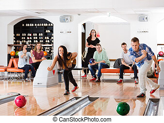 Young Friends Playing in Bowling Alley - Young friends...