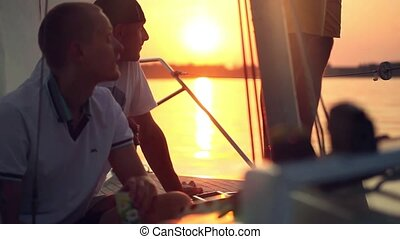 Young friends relaxing and drinking in sailing yacht at sunset. Traveling on a Yacht.
