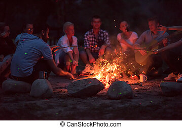 young friends relaxing around campfire - a group of happy ...