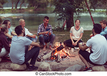 young friends relaxing around campfire - a group of happy...