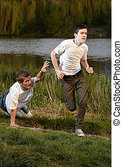 Young friends running - A young man fell in running next to...