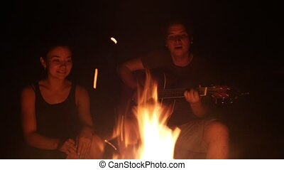 Young friends singing songs with guitar sitting by the campfire at the dark night