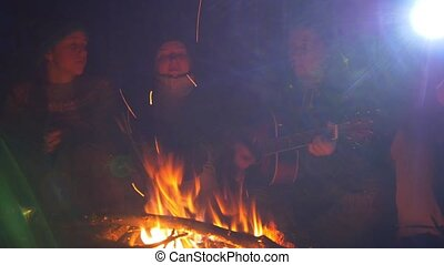 Young friends sitting at the campfire and playing guitar in...