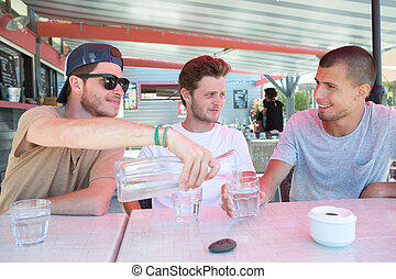 young friends sitting in a bar having a drink