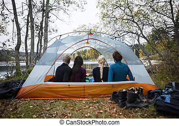 Young Friends Sitting In Tent On Lakeshore