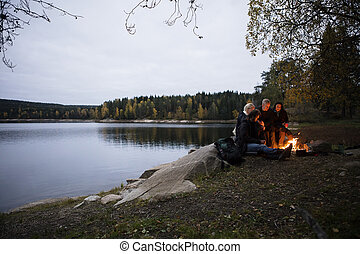 Young Friends Sitting Near Bonfire By Lake At Dusk