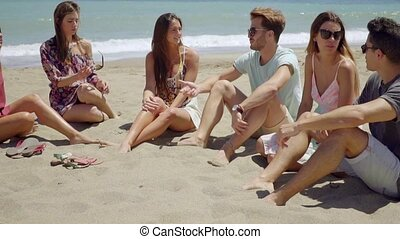 Young friends sitting on the beach chatting
