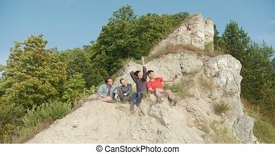 Young friends sitting on the cliff and making selfie outdoors