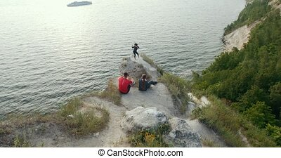 Young friends sitting on the mountain looking at beautiful woman dancing on the cliff by the sea
