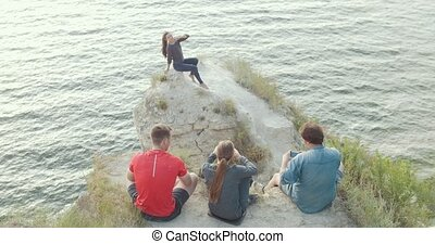 Young friends sitting on the mountain shooting a beautiful woman on the edge of a cliff