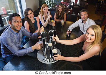 Young friends sitting together and pulling pints in a restaurant smiling at camera