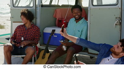 Young friends sitting together near camper van 4k