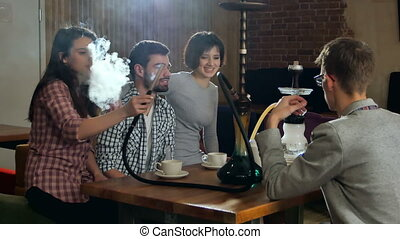 Young friends smoking hookah in shisha cafe. Professional...